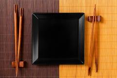 Den tomma svarta fyrkanten kritiserar plattan med pinnar för sushi på träbakgrund B?sta sikt med kopieringsutrymme arkivbilder