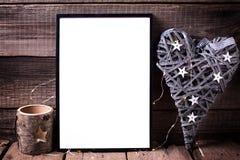 Den tomma svarta ramen, dekorativ hjärta och stearinljus på åldrigt uppvaktar Fotografering för Bildbyråer