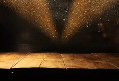 Den tomma tabellen framme av svart och guld blänker ljusbakgrund royaltyfria foton