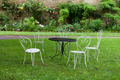 Den tomma tabellen och fyra vita stolar Royaltyfria Bilder