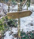 Den tomma träriktningsteckenstolpen med ingen text på den täckte i ett lager av snö under en snöstorm i julvintertid royaltyfria bilder