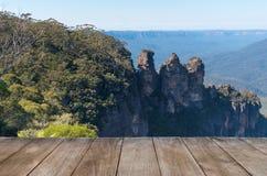 Den tomma trätabellen framme av Jamison Valley och tre systrar vaggar bildande i Katoomba, Australien royaltyfri foto
