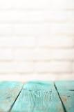 Den tomma trätabellen målade turkos- och vittegelstenväggcopysp Fotografering för Bildbyråer