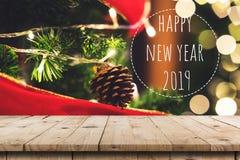 Den tomma trätabellen och jul sörjer kottar som hänger på julgranen och det lyckliga nya året 2019 med skärmmontagen för produkt royaltyfria foton