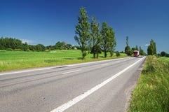 Den tomma vägen fodrade med poppelgränden i bygden, i avståndet som passerar den röda lastbilen Royaltyfria Bilder