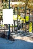 Den tomma vertikala affischtavlan, advertizingen, informationsbräde nära lurar lekplatsen i staden Fotografering för Bildbyråer