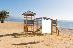 Den tomma vertikala affischtavlan, advertizingen, informationsbräde nära lurar lekplatsen på stranden Arkivbilder