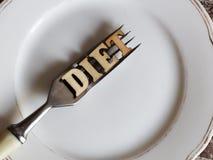 Den tomma vita plattan och gaffeln, bantar inskriften i träbokstäver Royaltyfria Foton