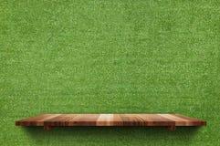 Den tomma wood brädehyllan på fejkar väggbakgrund för grönt gräs, åtlöje arkivbild