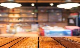 Den tomma wood tabellen och coffee shop gör suddig bakgrund med bokehimag Arkivfoto