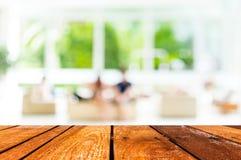 Den tomma wood tabellen och coffee shop gör suddig bakgrund med bokehimag Royaltyfri Foto