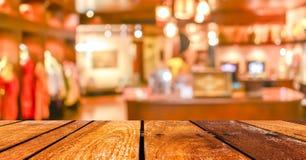 Den tomma wood tabellen och coffee shop gör suddig bakgrund med bokehimag Arkivbilder