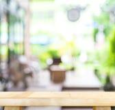 Den tomma wood tabellen och det suddiga kafét tänder bakgrund produktdisp Arkivfoton