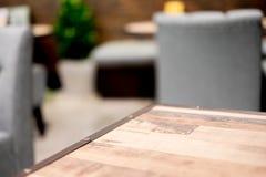Den tomma wood tabellen och det suddiga kafét tänder bakgrund produktdisp Royaltyfri Foto