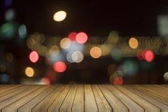 Den tomma wood tabellen och suddig bokeh ut ur fokus i natt tänder bakgrund produktskärmmall 3d business dimensional presentation Royaltyfri Foto