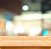 Den tomma wood tabellen och suddighetskafét tänder bakgrund Produktskärm Royaltyfria Bilder
