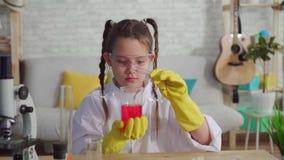 Den tonåriga bloggeren i ett vitt lag och exponeringsglas i laboratoriumet, blandar agens stock video