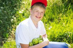 Den tonåriga blonda pojken rymmer gröna äpplen Fotografering för Bildbyråer