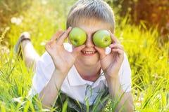Den tonåriga blonda pojken rymmer gröna äpplen Arkivbilder