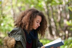Den tonåriga flickaläseboken i höst parkerar arkivfoto