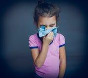 Den tonåriga flickan är sjuk nyser näsduken på en grå färg Royaltyfria Bilder