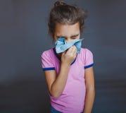 Den tonåriga flickan är sjuk nyser näsduken på grå färger Arkivbild