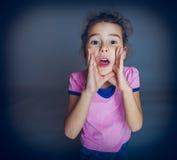 Den tonåriga flickan öppnade hennes munappeller på en grå färg Royaltyfri Fotografi