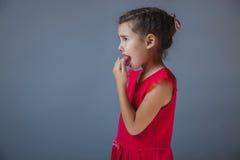 Den tonåriga flickan fingrar i hans röda klänning för munnen på en grå färg Royaltyfria Bilder