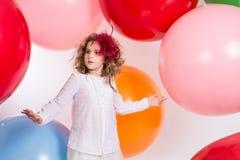 Den tonåriga flickan i en hatt och vit klär på en bakgrund av stor colore Royaltyfria Foton