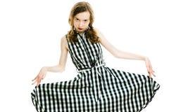 Den tonåriga flickan i svart rutig klänning och mörker utgör att posera royaltyfri foto