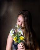 Den tonåriga flickan inhalerar arom av buketten av påskliljor Arkivbilder