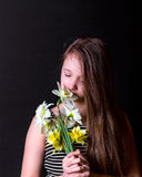 Den tonåriga flickan inhalerar arom av buketten av påskliljor Royaltyfri Foto