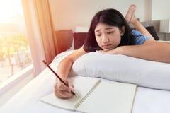 Den tonåriga flickan kopplar av att göra läxa hemma på säng i sovrum fotografering för bildbyråer