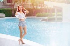Den tonåriga flickan kopplar av leendeanseende på simbassängferielivsstilen royaltyfri foto