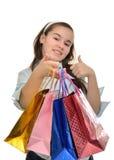 Den tonåriga flickan med mångfärgade packar i händer jublar köp Arkivbilder
