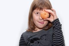 Den tonåriga flickan med mandarinen visar tonque Arkivbild
