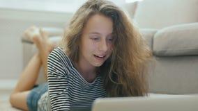 Den tonåriga flickan på en soffa läser från en bärbar dator, ler och ser till kameran stock video