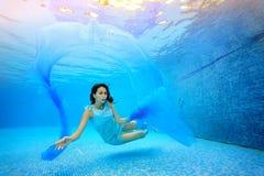 Den tonåriga flickan simmar undervattens- i pölen på en blå bakgrund, ser kameran och spelar med en blå torkduk Arkivbilder