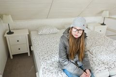 Den tonåriga flickan som sitter på sängmorgon, innan du går att skola - lat att starta arbetsdags- morgnar, är svår royaltyfria foton