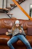 Den tonåriga flickan som sitter på soffan och att äta choklad - som är lat att göra något - morgnar är svår arkivbild
