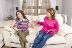 Den tonåriga flickan visar stoppgest till den ilskna modern, medan sitta på soffan hemma royaltyfria bilder