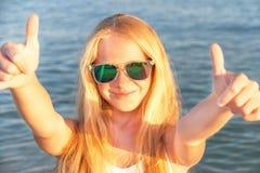 Den tonåriga flickavisningen tummar upp på havsbakgrunden royaltyfri bild
