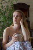 Den tonåriga kvinnan kopplar av koppen inom Royaltyfri Foto