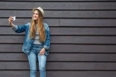 Den tonåriga kvinnasmartphonen får selfie utanför den wood väggen Royaltyfri Foto