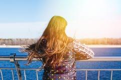 Den tonåriga lyckliga flickan kopplar av nära floden i stad parkerar utomhus- Royaltyfria Foton