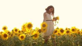 Den tonåriga lyckliga lilla flickan lukta en solros nyser allergiskt till blommor på fältet i sommar ultrarapidvideo flicka lager videofilmer