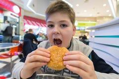 Den tonåriga pojken äter kafét för hamburgare n Fotografering för Bildbyråer