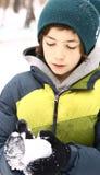 Den tonåriga pojken gör snö att klumpa ihop sig på vinter utomhus arkivfoton