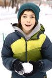 Den tonåriga pojken gör snö att klumpa ihop sig på vinter utomhus royaltyfri fotografi