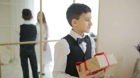 Den tonåriga pojken ger en flicka en gåva för en ferie, arkivfilmer